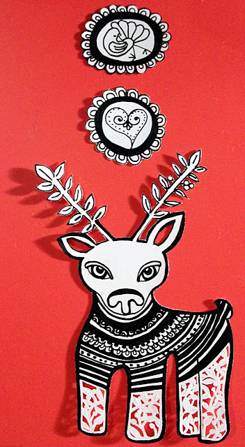 Black and white original drawing of a whimsical reindeer with paper cut out details set over a red background. It has two small ink drawings of a bird and a heart to glue to the ends of the strings to hang the reindeer with