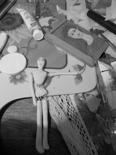 Black and white picture of my doll on the making, laying on my work area with craft related items