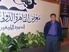 Di depan baliho Pameran Buku Internasional di Kairo