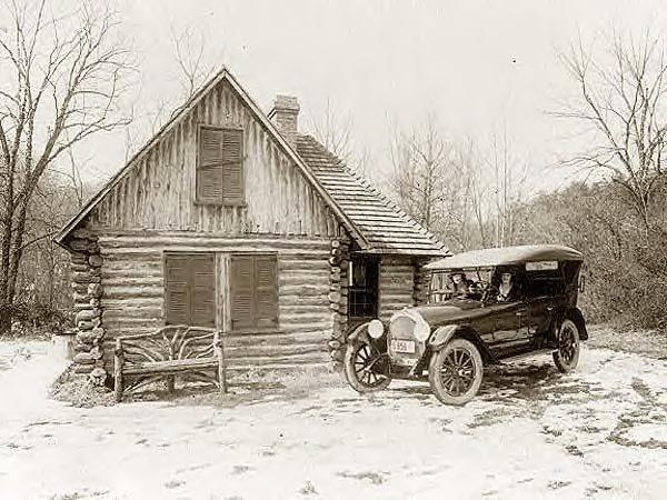 Log cabin, new Oldsmobile and 2 ladies. 1920