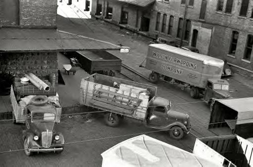 September 1939. Minneapolis, Minnesota. Trucks loading at farm implement warehouse