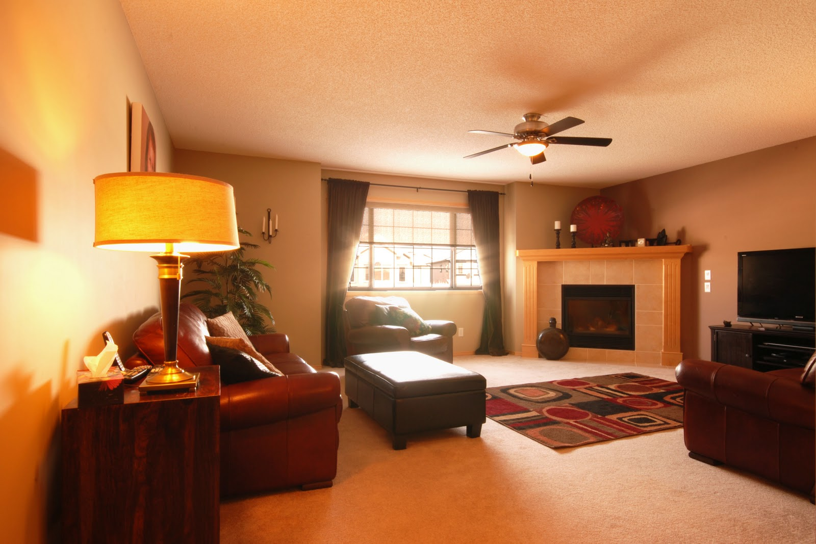 and a massive bonus room with corner gas fireplace and ceiling fan title=