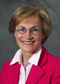 A head shot of Dr. Lylas Mogk, wearing a bright red suit and smiling