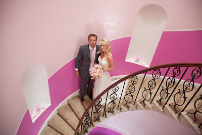 Bride and groom on pink staircase