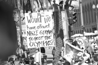 Protest sign which reads: would we have allowed nazi germany to host the olympics?