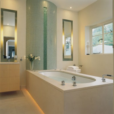 The curved wall of green glass makes a fine focal point, reminding bathers of a waterfall.