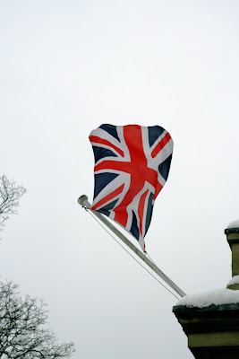Union Jack flag blowing in the snowy sky