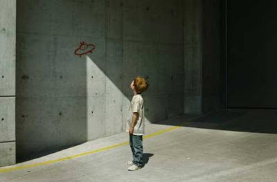 UFO graffiti painting on concrete wall with child by Banksy