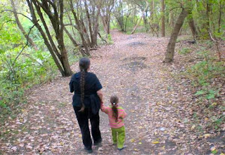 Mom and preschooler walking in the woods.