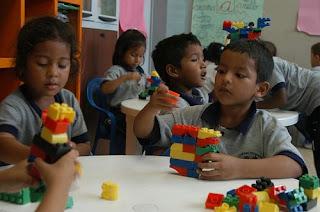 Niños y niñas jugando con piezas de construcción en un aula