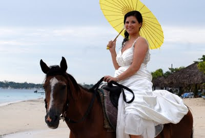 Woman in white gown with parasol on a horse on the beach