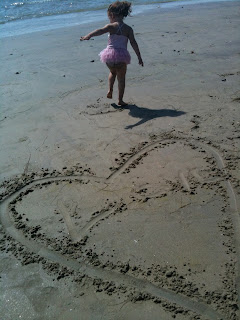 Child runs from site of a heart in the sand with word love in it