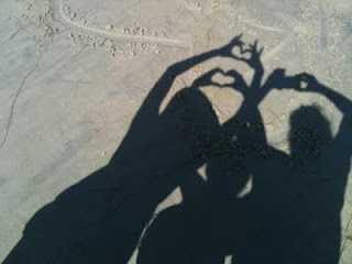 silhouettes of three people creating hearts with their hands