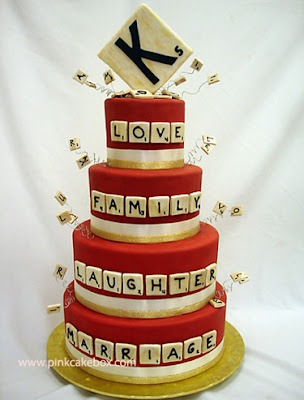 four-tier cake with Scrabble words and a big K tile at the top