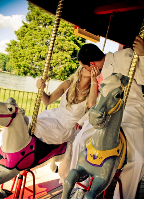 bride and groom riding carousel and kissing
