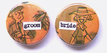one pin has a man's face and says groom and the other has a woman's face and says bride