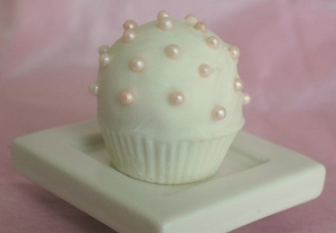 White cupcake with white pearls on a white plate