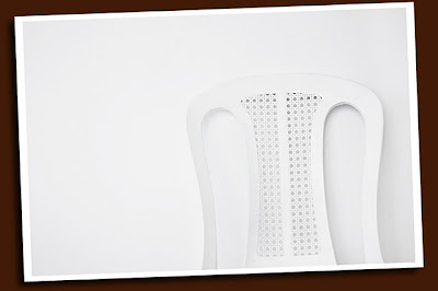 monoblock chair against white wall