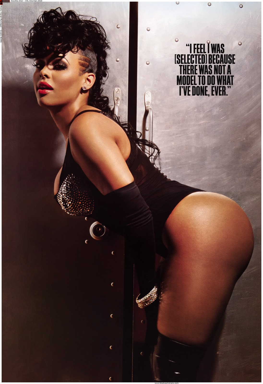Keyshia Dior behding over in a black leather one piece