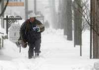 Letter carrier John Vazquez braves the snow as he delivers mail on his route Saturday, March 8, 2008 in Columbus, Ohio. A foot of snow buried parts of the Ohio and Tennessee valleys early Saturday, shutting down travel and many public events. Blizzard warnings remained in effect in Ohio, with winter storm warnings from Tennessee to upstate New York and northern Maine. Wind up to 35 mph whipped the snow and cut visibility to less than a quarter mile in places, the weather service said. (AP Photo/Kiichiro Sato)