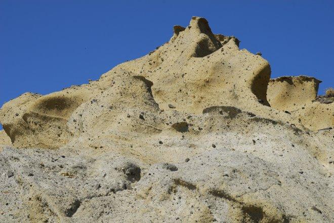 Una pared de roca volcánica. Más de uno ve una cara...