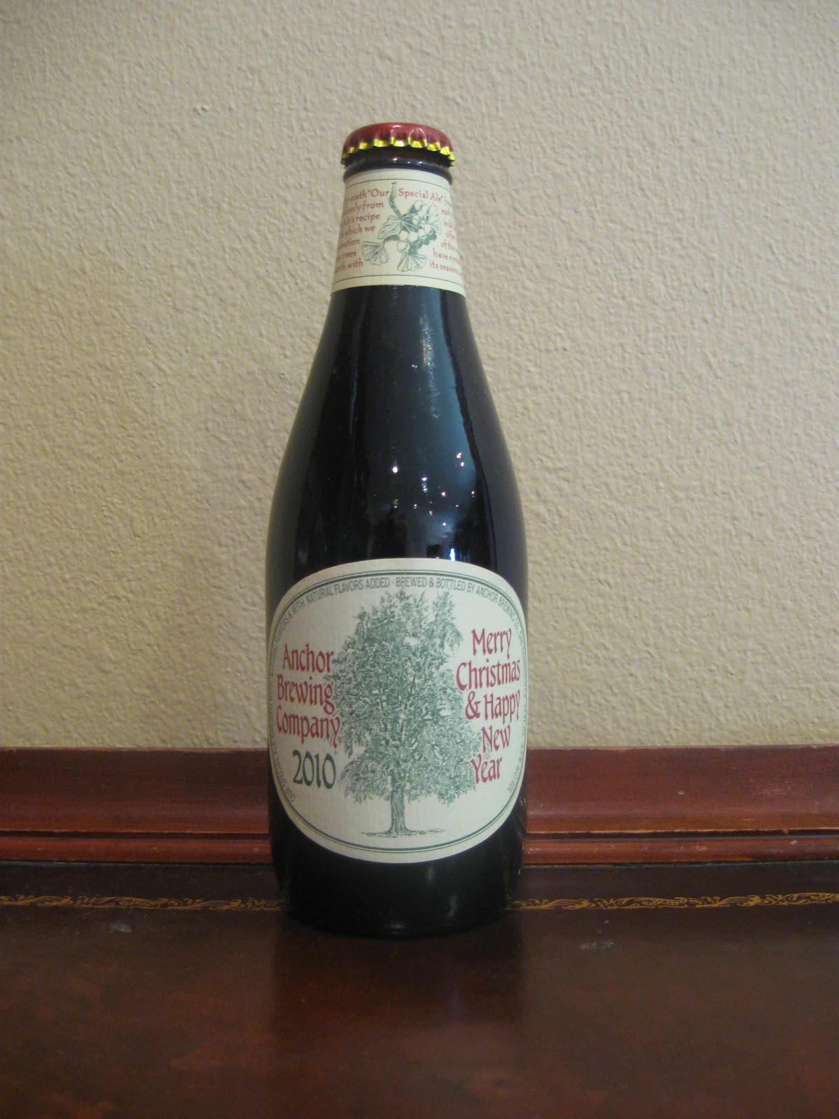 2012 the beer pours black in color tints of ruby if held to the light but essentially opaque there is a tall head of very light brown thick foam - Anchor Brewing Christmas Ale