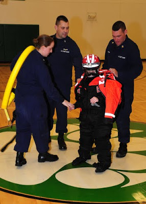 Petty Officer 3rd Class Ryan Levine, Master Chief Petty Officer Aaron Zimmer and Petty Officer 1st Class John Curtis, from Coast Guard Station Toledo, Ohio, help a student volunteer from Margaretta Elementary School dress out in Coast Guard ice rescue gear, Dec. 15, 2010. U.S. Coast Guard photo by Petty Officer 3rd Class George Degener