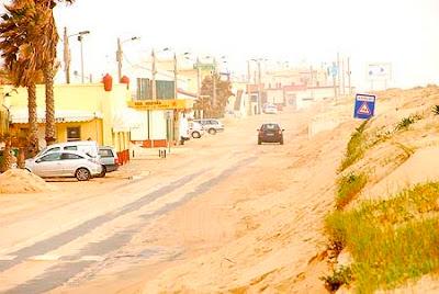 A estrada da zona nascente da Ilha de Faro bem como o parque de estacionamento à entrada da ilha estão inundados de areia proveniente da costa