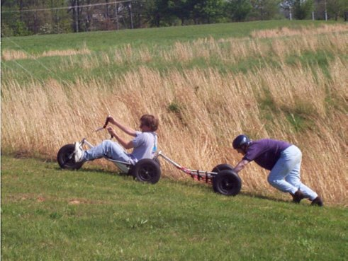 Tandem buggy being pushed up a hill