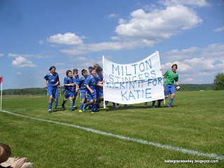 The Milton Stingers boys soccer team running with a Kickin it for Katie banner