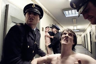 Two prisoners being hauled up a prison corridor