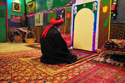 A Sufi Master Sitting down facing the Kaba