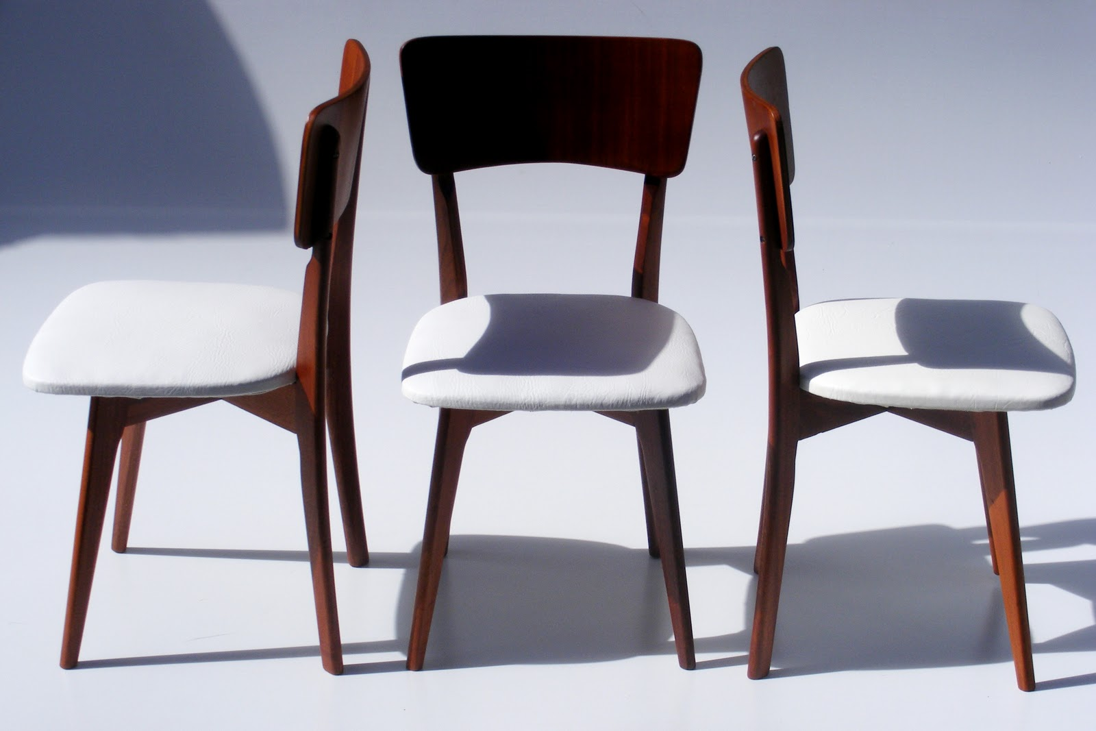 Retro dining chairs re covered in white vinyl