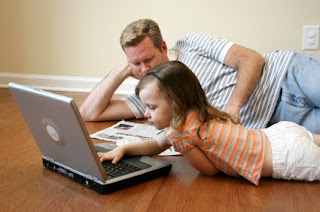 Dad and daughter reading newspaper and laptop