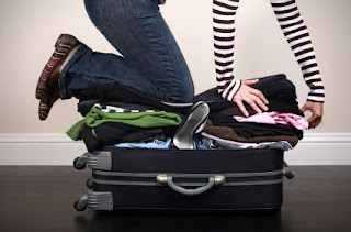 Girl kneeling on packed suitcase
