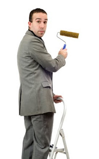 Businessman on a ladder with paint roller