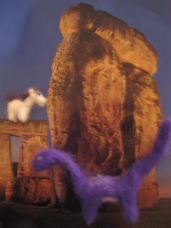 tiny felt dinosaur and tinier felt pony in front of a stonehenge background