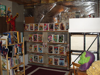 The light-wood shelves on the left hold books about comics (top two shelves),  comic strip collections (third shelf), and novels kind-of related to comic  ...