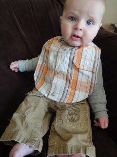 baby wearing orange plaid shirt bib