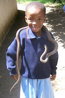 grinning little boy with a snake draped over his shoulders