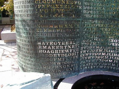 GRANITE LOW FOUNTAIN: Kryptos is a 9-foot 11-inch-high main sculpture—an S-shaped wave of copper with cut-out letters, anchored by an 11-foot column of petrified wood—and huge pieces of granite abutting a low fountain