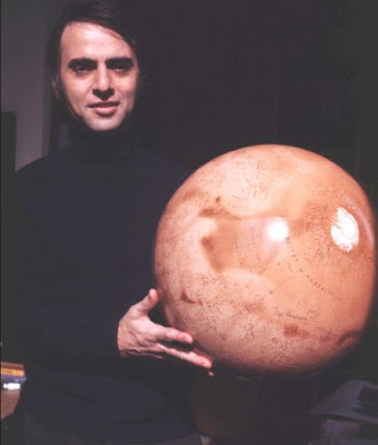 Carl Sagan with globe of Mars