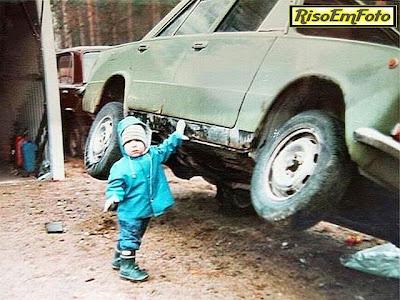 Criança pequena erguendo automóvel.