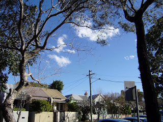 blue sky with a few scant white clouds seen above a row of houses