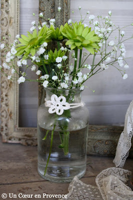 Some flowers mixed with sprigs of gypsophilia in a old glass bottle
