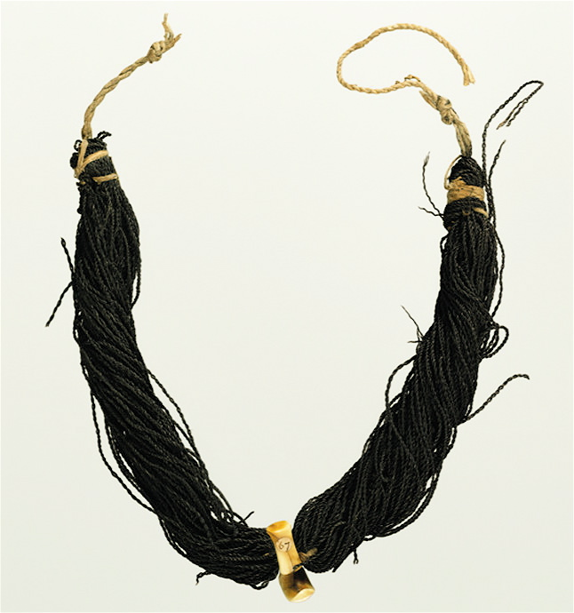 whale tooth pendants suspended from braided strands of human hair were