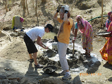 INDIA: Volunteers mixing cement and carrying it to the wall-like structure.