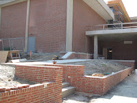 Brickwork lining the new ramp to the loading dock is put into place.