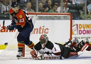 Florida Panthers Brett McLean (L) looks for a rebound as New Jersey Devils goaltender Kevin Weekes falls to the ice during first period NHL ice hockey game in Sunrise, Florida, October 6, 2007. REUTERS/Hans Deryk (UNITED STATES)