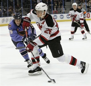 New Jersey Devils left wing Patrik Elias (26), of the Czech Republic, takes a shot as Atlanta Thrashers forward Marty Reasoner (19) defends during the second period of an NHL hockey game Thursday, Oct. 16, 2008, in Atlanta. New Jersey won 1-0.<br />(AP Photo/John Amis)